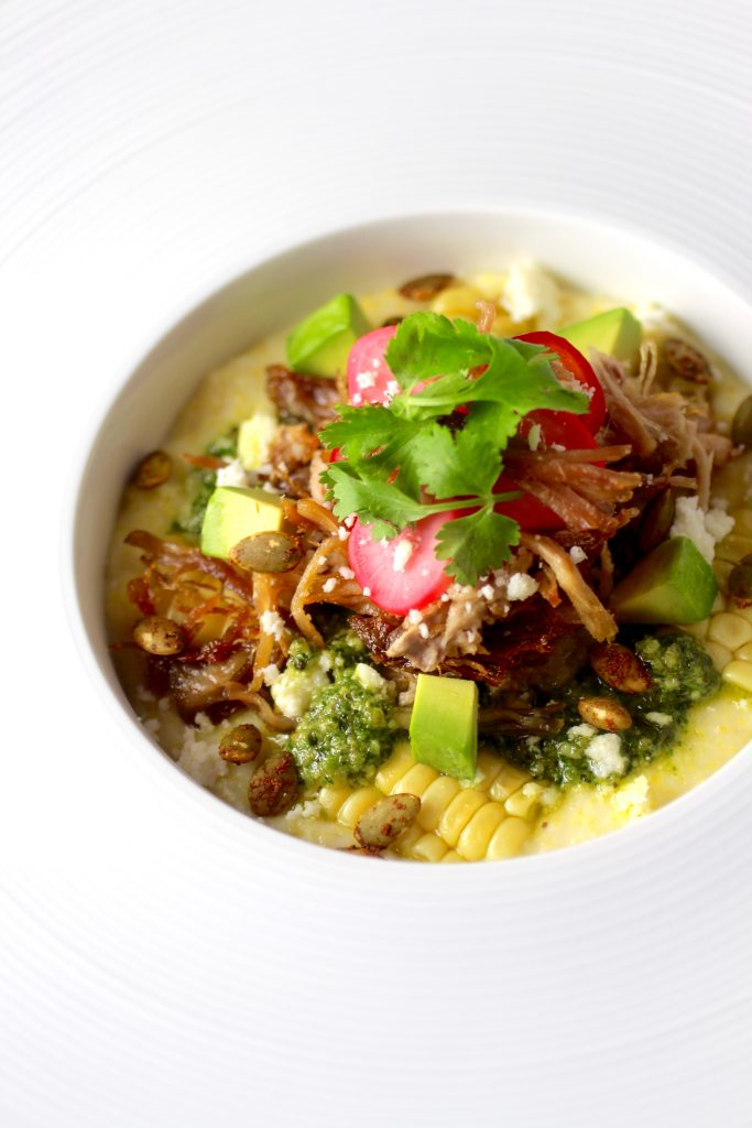 Carnitas, Polenta, Pumpkin Seed Kale Cilantro Pesto, Avocado, Fresh Corn, Spicy Pumpkin Seeds, Mexican Crema, Pickled Radish and Red Jalapeno, Cilantro, Cotija Cheese